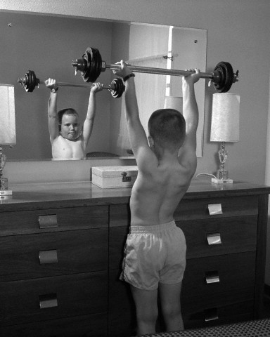 12 Jan 1965 --- Boy exercising with dumbbell at mirror in bedroom --- Image by © B. TAYLOR/ClassicStock/Corbis