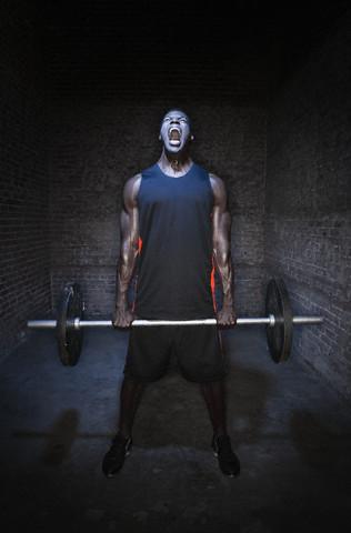 Man lifting weights --- Image by © Walter Lockwood/Corbis